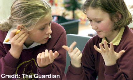 Two elementary school girls using their fingers to count | Credit: The Guardian