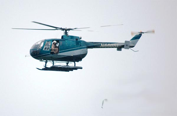 A helicopter deploys acetaminophen-treated dead mouse baits in Guam [Credit: USDA/APHIS]