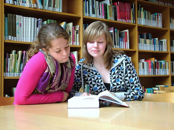 Two girls reading a book at a table in the library [Credit: Ziko van Dijk, Wikimedia Commons]